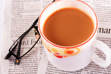 Tea cup with a news paper and spectacles