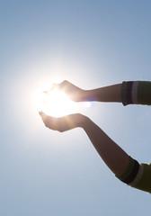 Woman's hands holding sun