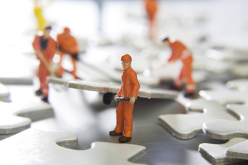 Worker figurines placed with puzzle pieces
