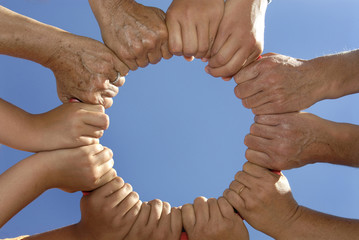 Several hands holding together in a circle