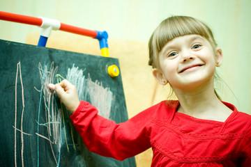 Girl draws with chalk on the blackboard