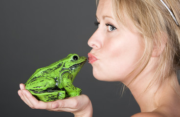 Shot of a Pretty Blonde Girl Kissing a Frog