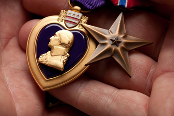 Man Holding Purple Heart and Bronze War Medals