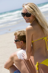 A woman rubbing sunscreen on her boyfriend