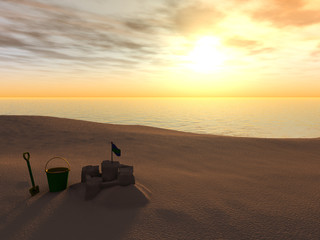Bucket, spade and sand castle on a beach at sunset.