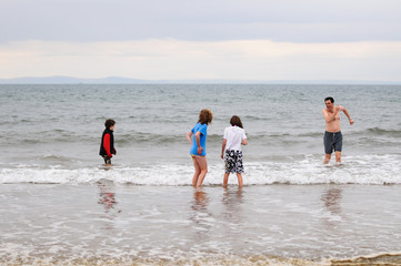 father and children wading in cold sea