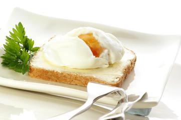 pochiertes Ei auf Toast, Messer und Gabel