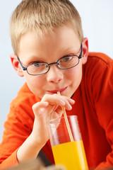 Child sipping orange juice through straw.