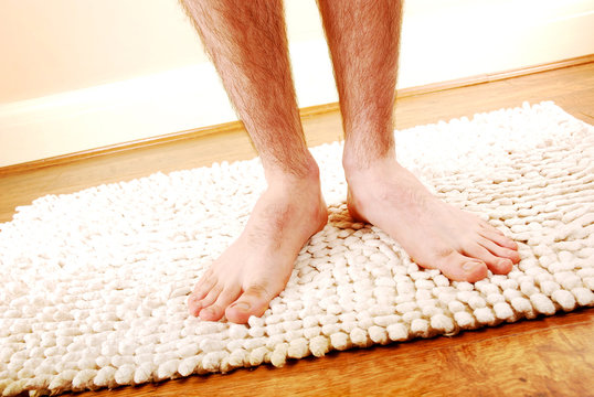 Man's legs on a bathmat