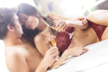 Couple kissing and drinking champagne on the bed