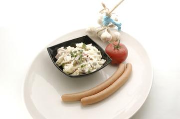 Nudelsalat in einer schwarzen Schale und Wuerstchen und Tomate