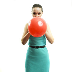Young attractive girl inflating a balloon