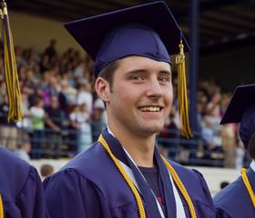 Male high school graduate attending graduation ceremony