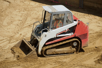 A small tracked skid loader at a construction site
