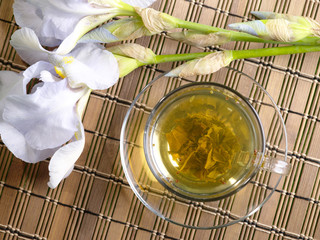 cup of green tea with flower on bamboo background