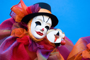 Clown holding his mask