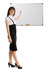 Young woman in businesssuit pointing on whiteboard