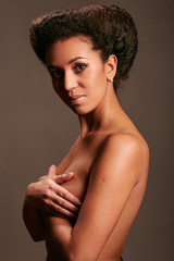 Young beautiful black naked woman on gray background