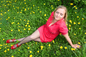 Young girl sitting in dandelion meadow