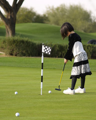 A young girl has fun playing golf on a beautiful green.