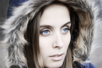Portrait of a beautiful blue eyed young woman with a hood