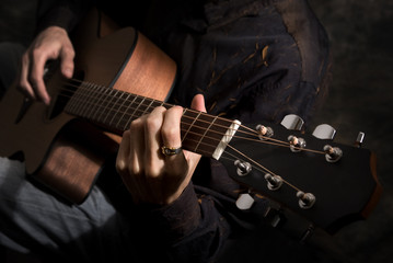 man playing acoustics guitar