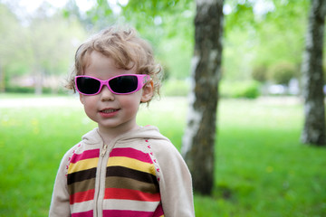 small girl with sunglasses in nature