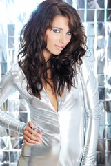 beautiful brunette girl wearing silver dress on light background