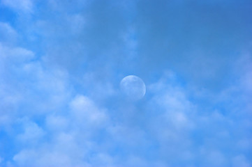 moon peeking out on an afternoon above the clouds