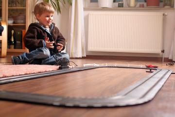 Kleiner Junge mit Autorennbahn