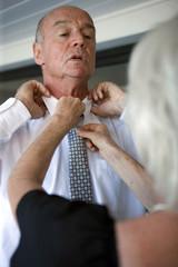Femme aidant un homme âgé à se préparer