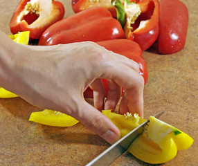 Female hands cut pepper