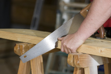 carpenter cuts a plank with a saw