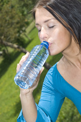 Portrait of lyoung girl holding bottle of water in hand