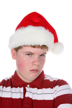 grouchy looking teenage boy in stanta hat and a scowl