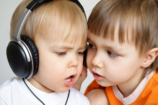 Two singing boys. One with black headphones