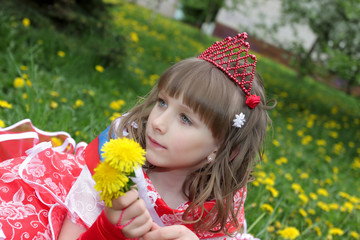 The girl in red dress with dandelions on lawn