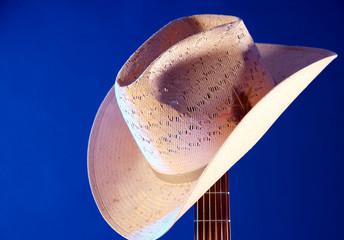 Western hat on Guitar Neck Against Blue