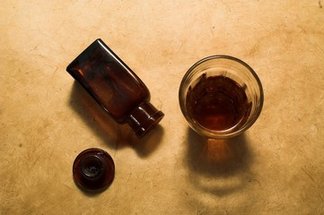 Medicin bottle and glas with brown liquide from above.