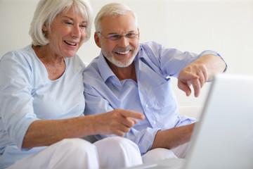 Couple de seniors souriants devant une webcam