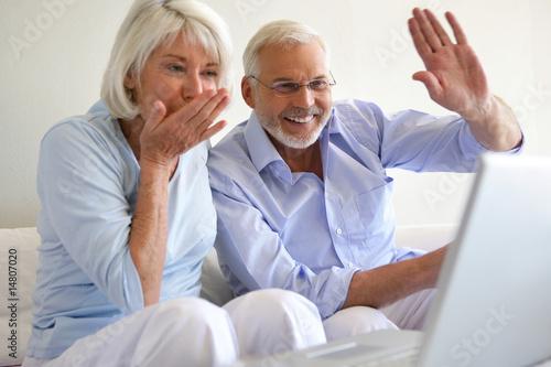 couple de seniors assis devant un ordinateur portable photo libre de droits sur la banque d. Black Bedroom Furniture Sets. Home Design Ideas