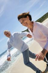 Portrait d'un couple de seniors courant au bord de la plage
