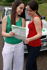 Teenage girl showing her friend driving test results