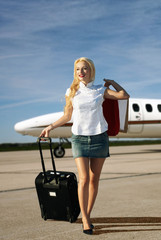 The girl with luggage going from plane