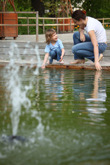 Mother with daughter in park at pool with fountain touch water