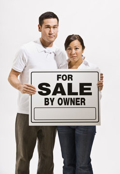 Worried Couple Holding For Sale Sign