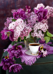 cup of coffee and a bouquet of lilacs