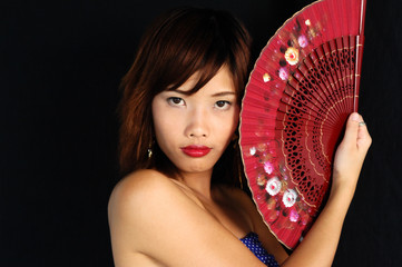 Very seductive young asian woman with a fan