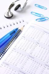 Kugelschreiber, Büroklammer, Kopfhörer und Kalender