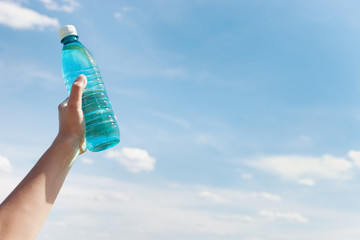 Hand holding bottle of water against blue sky